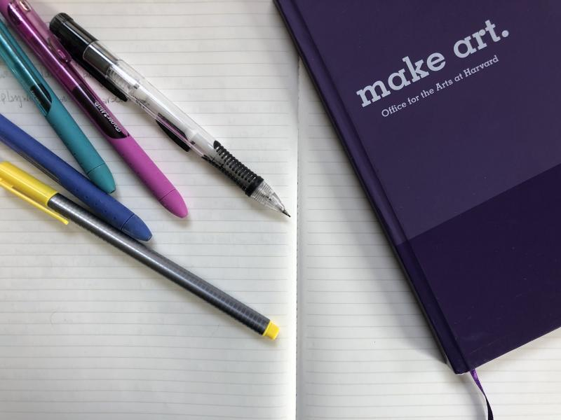 """An open notebook. On top there is another purple notebook that says """"Make Art"""" on the cover, along with a variety of pens and pencils."""