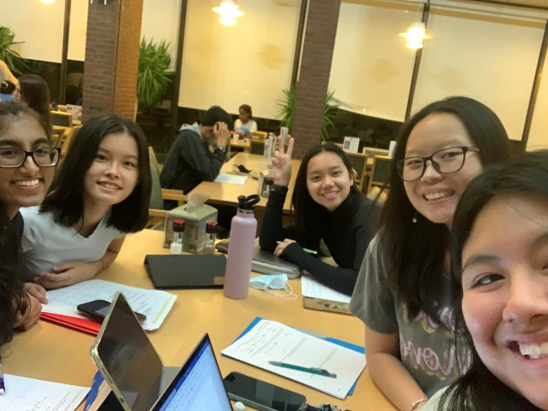 Five girls studying in a college dining hall.