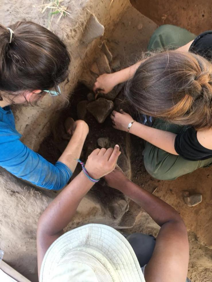 three students working in an excavation unit