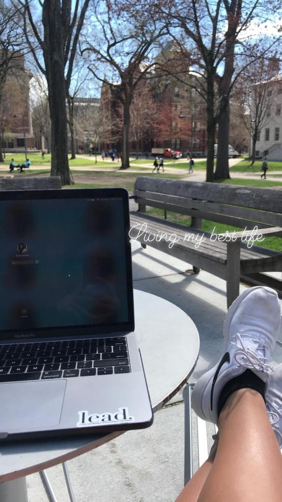 student studying outside with text that reads: 'Living my best life'