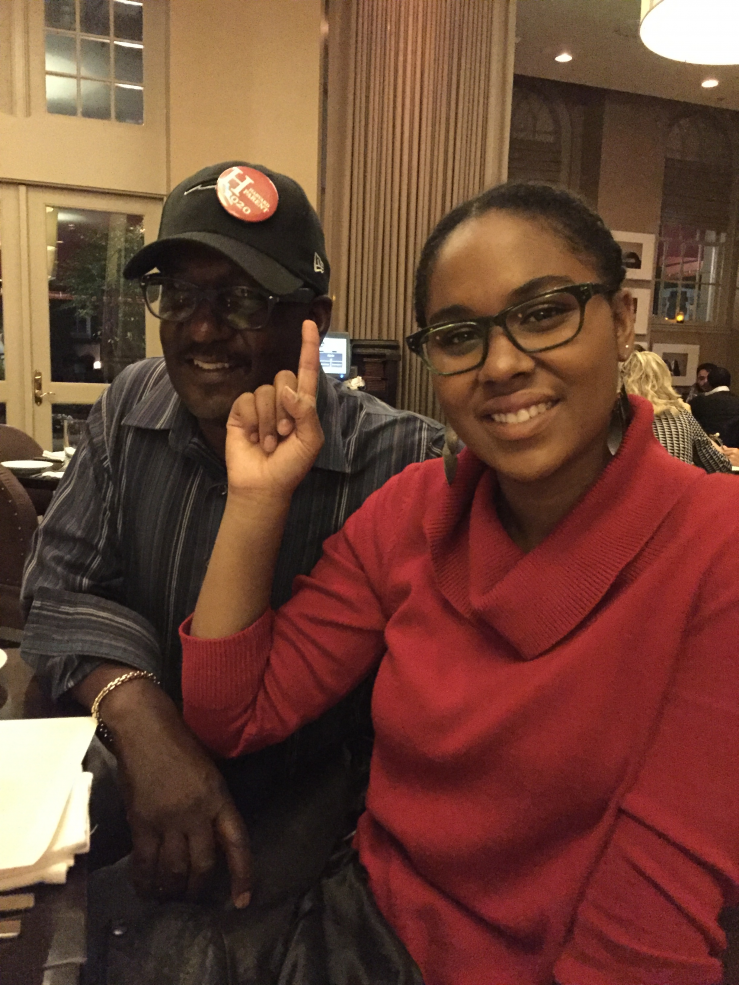 Student with her father who wears a Harvard Parent 2020 pin