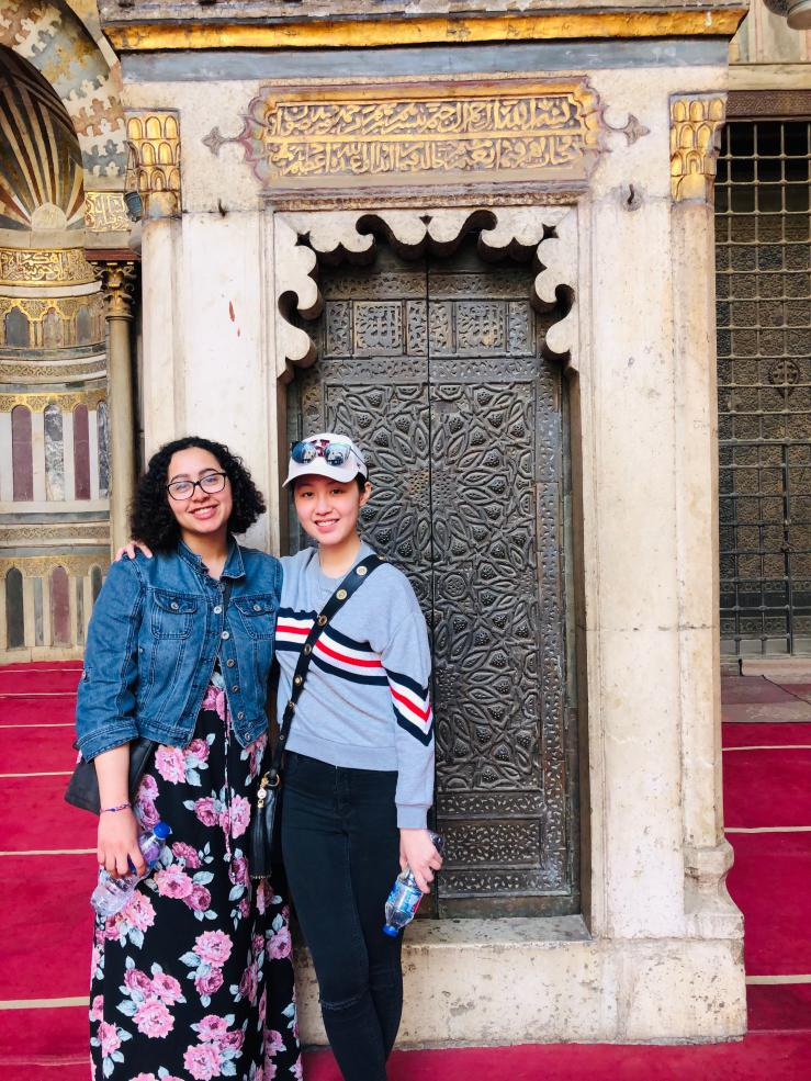 Two students in front of a mosque
