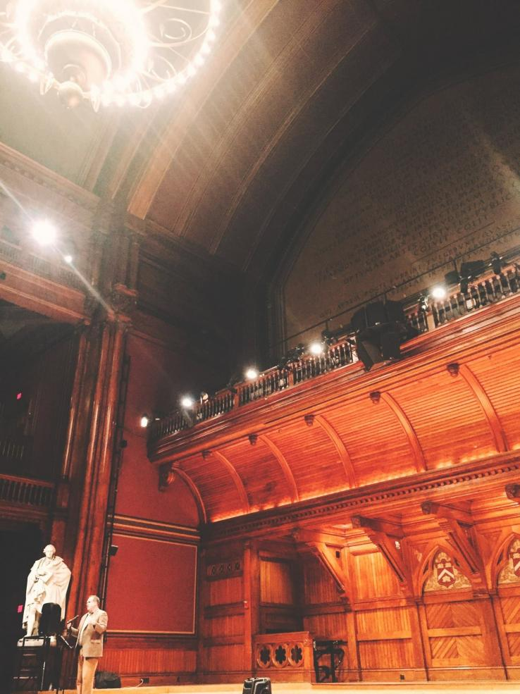 a man standing on stage in Sanders Theatre
