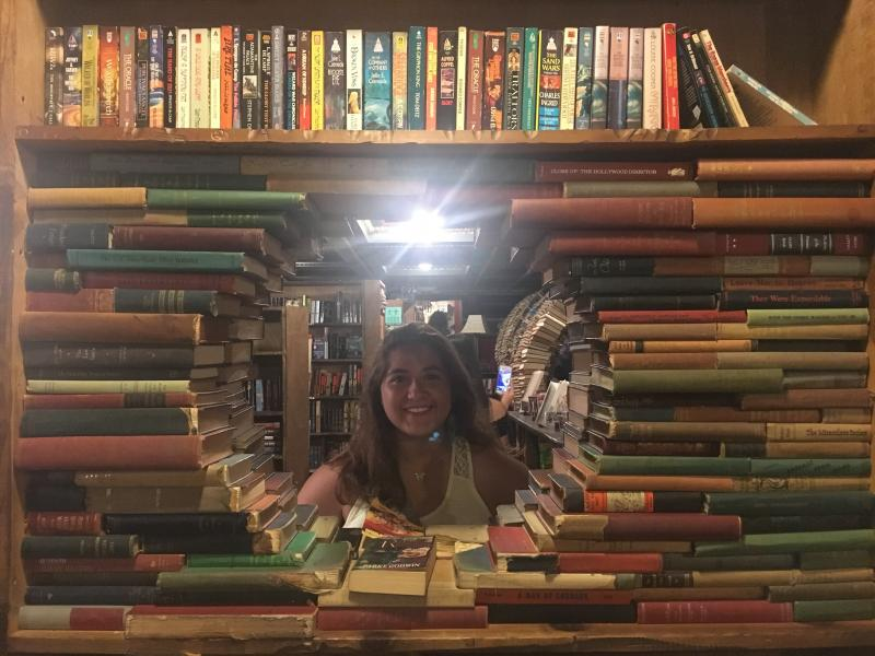 a student and bookshelves in bookstore