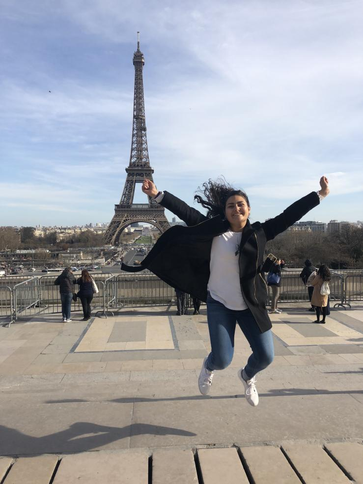 student jumping in front of the Eiffel Tower