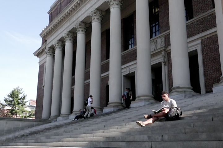 Student on studying on steps of Widener Library
