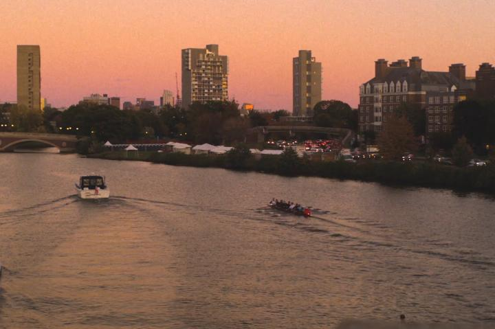 A series of boats rows down the Charles River at dawn.