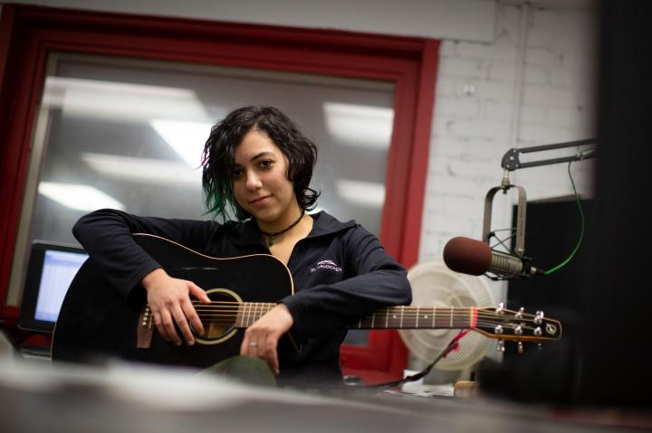 Emily Spector has taken songwriting classes on both sides of the river. She is sitting here holding a guitar