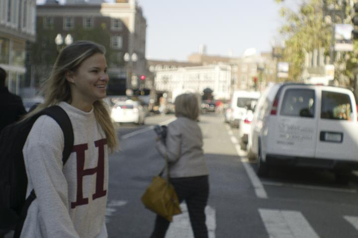 A student wearing an H sweatshirt walking across Harvard Square
