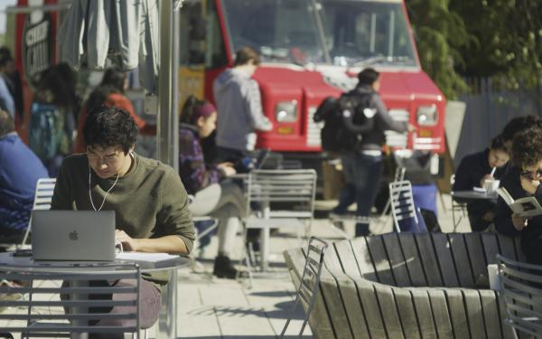 A student in a green sweater sits at a laptop at an outside table. Students in the background are getting lunch from a foodtruck.