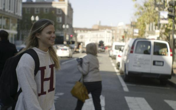 Student wearing Harvard sweatshirt walking towards Harvard Yard