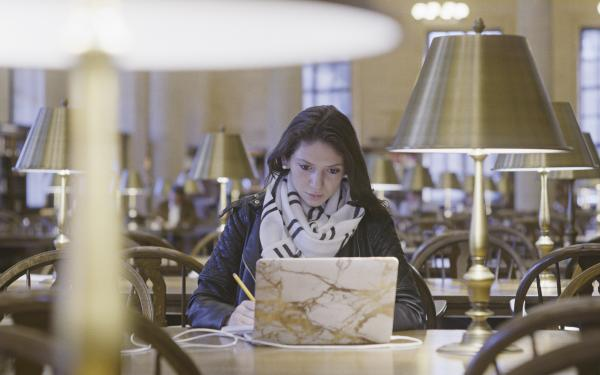Female student working at a laptop in Widener library