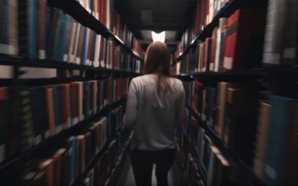 Student walking through library stacks