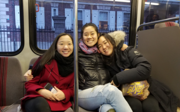 three students riding the subway