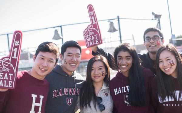 Six Harvard students with foam fingers cheering for Harvard-Yale football game