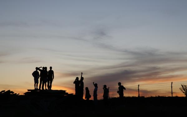 Silhouette of a group of people against a sunset background