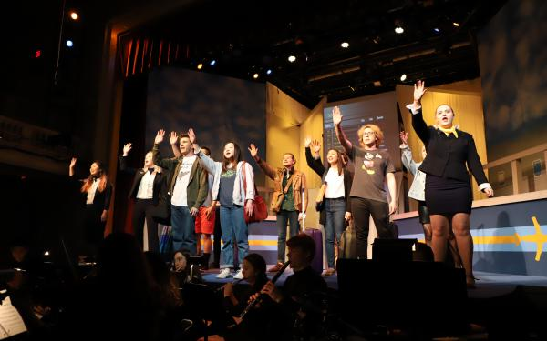 Actors on stage raising their hands singing, with musicians below