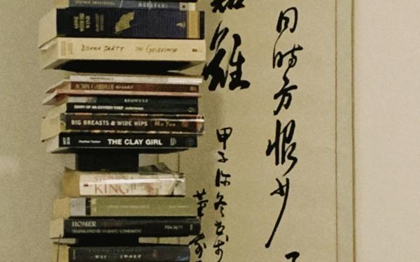 Stack of Books in Front of Painting
