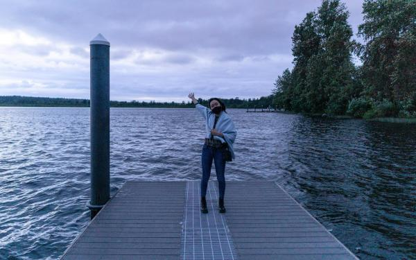 I am posing happily by a lake in my hometown near Seattle, WA. It's really cloudy and getting dark.