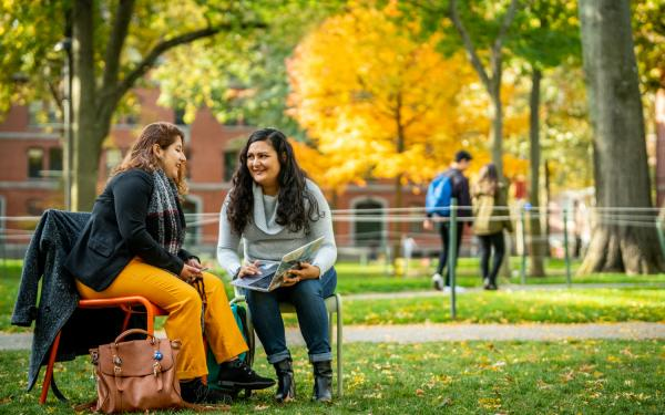Two Students Sitting in Harvard Yard in the Fall