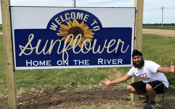 Picture of Harpreet next to the Sunflower County Sign