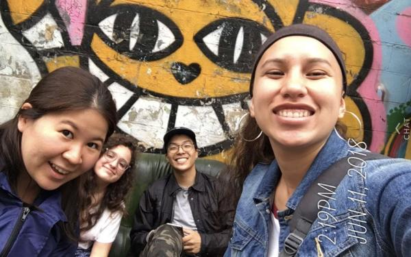 4 students in front of wall art in Paris.