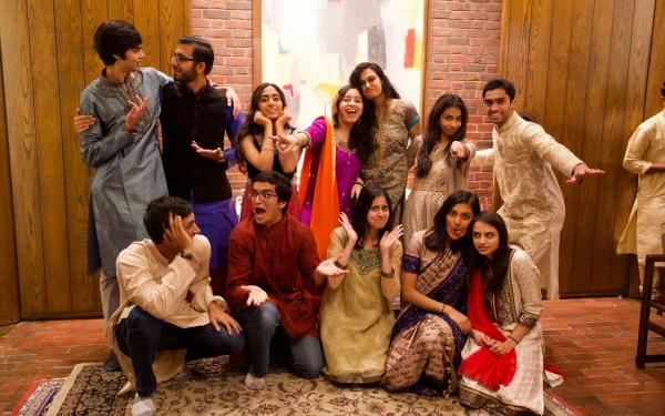 Group of students wearing Indian clothes indoors posing and smiling