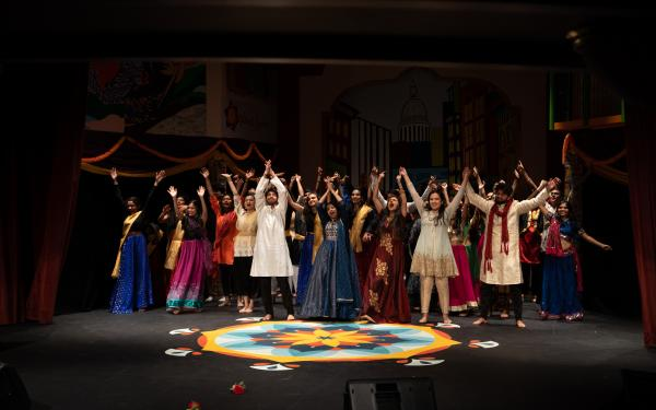 Students wearing South Asian clothing all preparing to bow on stage in the finale of Harvard Ghungroo 2020, with a Rangoli set in front of them.