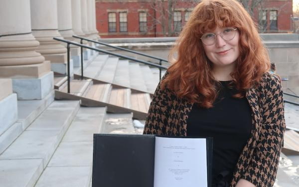 Allison standing on the steps of a large library holding a black thesis binder opened to the title page of her thesis.