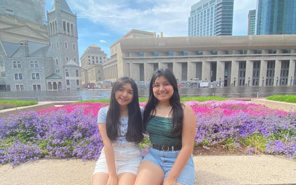 Two girls sitting by flower beds.