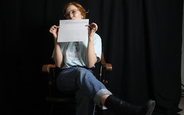 student in a chair and holding a piece of paper